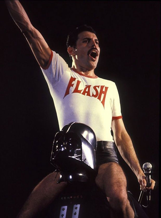 Freddie-Mercury-on-stage-riding-Dark-Vador,-1980